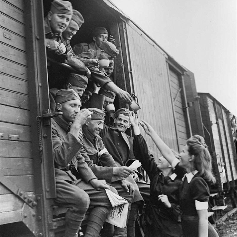 """Jozef Teslík - """"Haemistky"""" podávajú vojakom na slovenských staniciach čaj. Odchod vojakov na východný front, 1941, Slovenský národný archív, Bratislava – fond STK"""